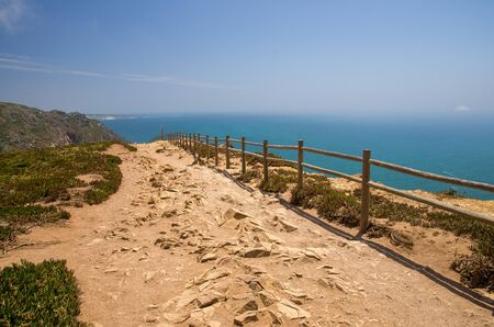 Portugal, Cabo da Roca, The Western Cape Roca of Europe,  hiking trails on the Cape Roca, ocean view from the Cape  Roca, cliff above the Atlantic ocean, azure water in the Atlantica, wooden handrails over the cliff Stock Photo