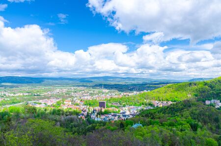 Top aerial panoramic view of Karlovy Vary (Carlsbad) spa town with colorful beautiful buildings, Slavkov Forest with green trees and Ore Mountain range background, West Bohemia, Czech Republic