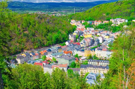 Karlovy Vary (Carlsbad) historical city centre top aerial view with colorful beautiful buildings, Slavkov Forest hills with green trees and Ore Mountain range background, West Bohemia, Czech Republic