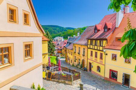 Enge Straße der Stadt Loket, farbenfrohe traditionelle typische Gebäude mit bunten Wänden, Kopfsteinpflaster, Holzzaun, grüner Hügelhintergrund, Region Karlovy Vary, Westböhmen, Tschechien