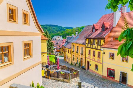 Loket town narrow street, colorful traditional typical buildings with multicolored walls, cobblestone road, wooden fence, green hills background, Karlovy Vary Region, West Bohemia, Czech Republic