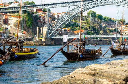 Portugal, Porto, wooden boats with wine barrels on Douro river close up, wooden boats with port barrels close up on Douro river, Porto old town view, The Eiffel Bridge, Ponte Dom Luis