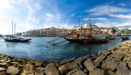 Portugal, city landscape Porto, wooden boats with wine port barrels on Douro river, panoramic view of the old town Porto,  The Eiffel Bridge view, Ponte Dom Luis, Porto in summer, colored houses