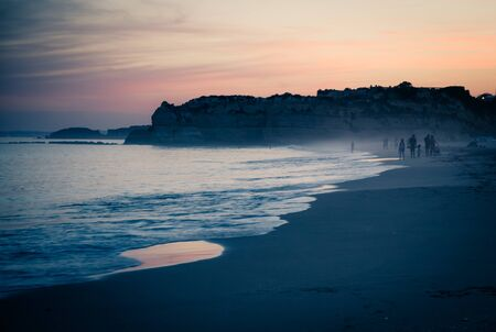 Portugal, Algarve, The best beaches of Portimao, Praia da Rocha, lilac golden sky at sunset over the waves of The Atlantic Ocean, a man playing with his dog on the beach, evening panorama of the city