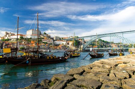 Portugal, city landscape Porto, a group of yellow wooden boats with wine port barrels on Douro river, panoramic view of the old town Porto, The Eiffel Bridge view, Ponte Dom Luis, stone embankment
