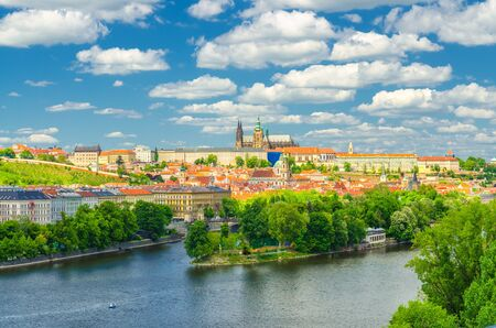 Aerial panoramic view of Prague city, historical center with Prague Castle, St. Vitus Cathedral in Hradcany district, Strelecky island, Vltava river, blue sky white clouds, Bohemia, Czech Republic