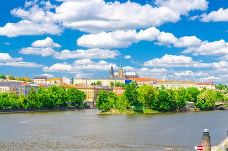 View of Prague old town, historical center with Prague Castle, St. Vitus Cathedral in Hradcany district, Strelecky island green trees, Vltava river, blue sky white clouds, Bohemia, Czech Republic