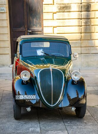 Lecce, Italy - April 23, 2016: Front view of vintage classic retro black automobile car parked in a street of Lecce city, Puglia Apulia region, Southern Italy