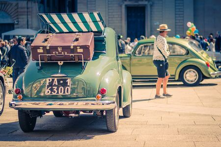 Lecce, Italy - April 23, 2017: Back view of green vintage classic retro car with a bag on top at the central square Piazza del Duomo during exhibition, Puglia Apulia region, Southern Italy Stock Photo