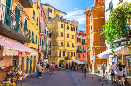 Riomaggiore, Italy, September 9, 2018: people tourists walking down street with multicolored colorful buildings houses of typical traditional village in National park Cinque Terre, Liguria, Italy