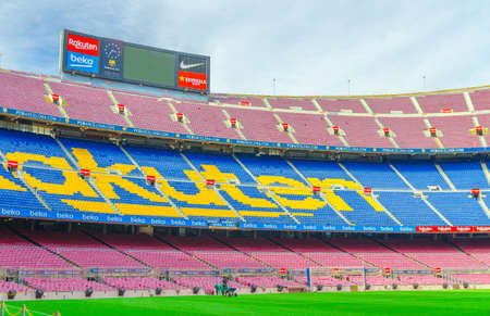 Barcelona, Spain, March 14, 2019: Camp Nou is the home stadium of football club Barcelona, the largest stadium in Spain. View of tribunes stands, green grass field and scoreboard from reserves bench. Editorial