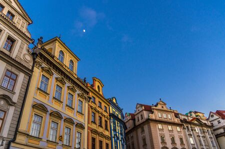 Row of buildings with colorful facades in Prague Old Town Stare Mesto historical city centre on Old Town Square Staromestske namesti in evening, blue sky and moon background, Bohemia, Czech Republic