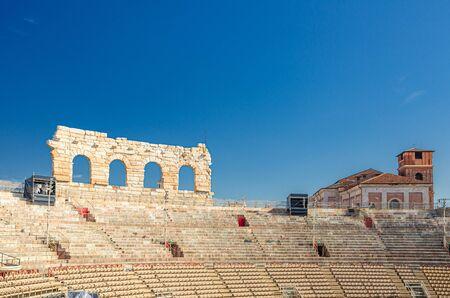 The Verona Arena interior inside view with stone stands. Roman amphitheatre Arena di Verona ancient building, sunny day, blue sky, Verona city historical centre, Veneto Region, Northern Italy