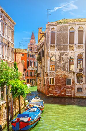Venice cityscape with narrow water canal Rio de San Agostin with colorful boats moored between old buildings, Veneto Region, Northern Italy. Typical Venetian view, vertical view, blue sky background