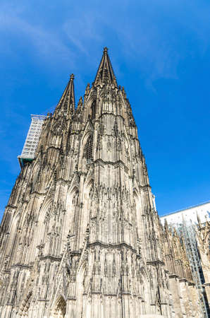 Cologne Cathedral Roman Catholic Church of Saint Peter gothic architectural style building with two huge spires in historical city centre, blue sky in sunny day, North Rhine-Westphalia, Germany
