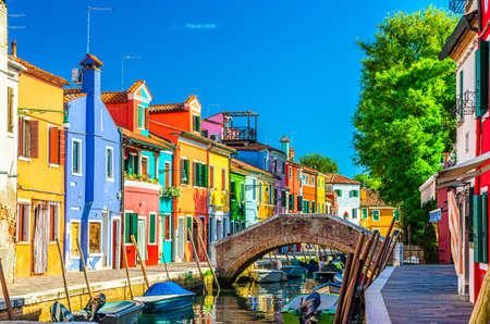 Colorful houses of Burano island. Multicolored buildings on fondamenta embankment of narrow water canal with fishing boats and stone bridge, Venice Province, Veneto Region, Italy. Burano postcard