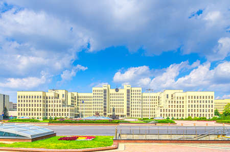 The Government House constructivism style building and Vladimir Lenin statue on Independence Square in Minsk city historical centre, blue sky white clouds in sunny summer day, Republic of Belarus
