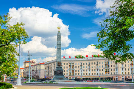 Victory Square in Minsk city centre with Granite Monument of Victory and red letters on the building read immortal , blue sky white clouds in sunny day, Republic of Belarus