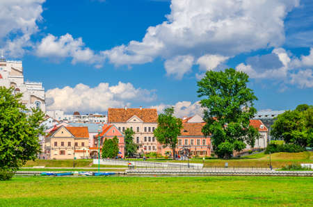 Traeckaje Suburb with old buildings in Trinity Hill district and grass lawn with green trees in Minsk city historical centre, blue sky white clouds in sunny summer day, Republic of Belarus