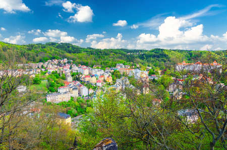 Karlovy Vary Carlsbad historical city centre top aerial view with colorful beautiful buildings, Slavkov Forest hills with green trees, blue sky white clouds background, West Bohemia, Czech Republic Reklamní fotografie
