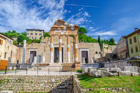Capitolium of Brixia or Temple of Capitoline Triad or Tempio Capitolino ruins and Santuario Repubblicano, Brescia city historical center, Cidneo Hill green trees background, Lombardy, Northern Italy