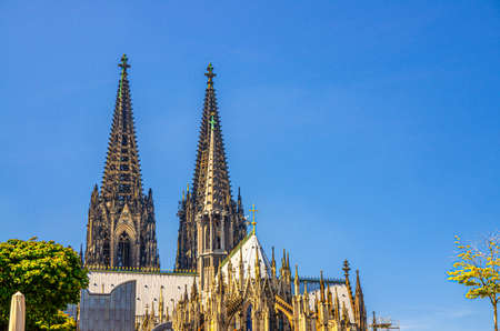 Two huge spires of Cologne Cathedral Roman Catholic Church Saint Peter gothic architectural style building in historical city centre, blue sky in sunny day copy space, North Rhine-Westphalia, Germany