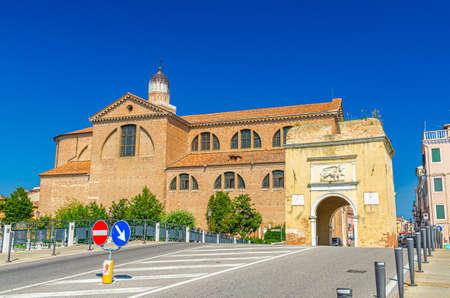 Porta Santa Maria o Porta Garibaldi gate and Cathedral Santa Maria Assunta Duomo Catholic Church in Chioggia town historical center, blue sky background in summer day, Veneto Region, Northern Italy