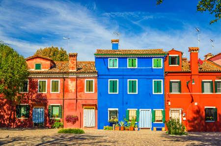 Colorful houses of Burano island. Multicolored buildings in small cobblestone square, blue sky background in sunny summer day, Venice Province, Veneto Region, Northern Italy. Burano postcard Foto de archivo