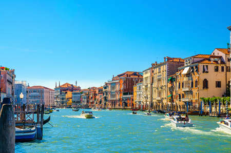 Venice cityscape with Grand Canal waterway, Venetian architecture colorful buildings, gondolas and yacht boats sailing Canal Grande, blue sky in sunny summer day. Veneto Region, Northern Italy. Stockfoto
