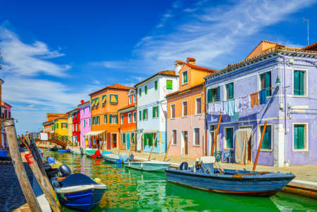 Colorful houses of Burano island. Multicolored buildings on fondamenta embankment of narrow water canal with fishing boats and wooden bridge, Venice Province, Veneto Region, Northern Italy