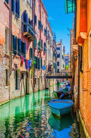 Venice cityscape with narrow water canal with boats moored between old colorful buildings and bridge, Veneto Region, Northern Italy. Typical Venetian view, vertical view, blue sky background
