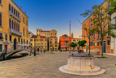 Campo San Vio with Palazzo Cini and Palazzo Barbarigo palaces, stone well and bridge across narrow water canal, buildings on Grand Canal waterway in Venice historical city center background, Italy