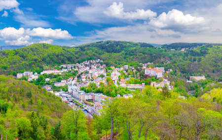 Karlovy Vary city aerial panoramic view with row of colorful multicolored buildings and spa hotels in historical city center. Panorama of Karlsbad town and Slavkov Forest mountains, Czech Republic
