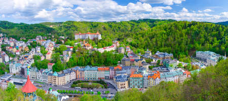 Karlovy Vary city aerial panoramic view with row of colorful multicolored buildings and spa hotels in historical city center. Panorama of Karlsbad town and Slavkov Forest mountains, Czech Republic Stock Photo