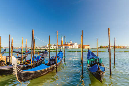 Gondolas moored docked on water in Venice. Gondoliers sailing San Marco basin waterway. San Giorgio Maggiore island with Campanile San Giorgio in Venetian Lagoon, blue clear sky, Veneto Region, Italy