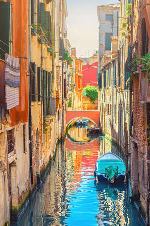 Venice cityscape with narrow water canal with boats moored between brick walls of old buildings and stone bridge, Veneto Region, Northern Italy. Typical Venetian view, vertical view
