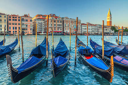 Gondolas moored in water of Grand Canal waterway in Venice. Baroque style colorful buildings along Canal Grande and bell tower Campanile di San Marco. Typical Venice cityscape, Veneto Region, Italy
