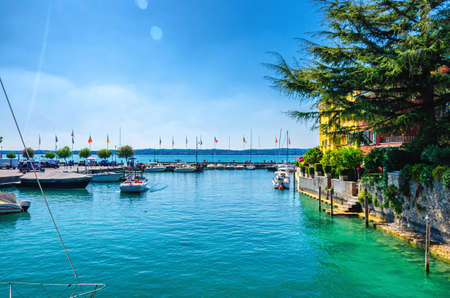 Harbor of Garda lake with blue azure turquoise water, wooden pier dock and yacht, motor boats, coast and blue sky background, Sirmione town, Lombardy, Northern Italy