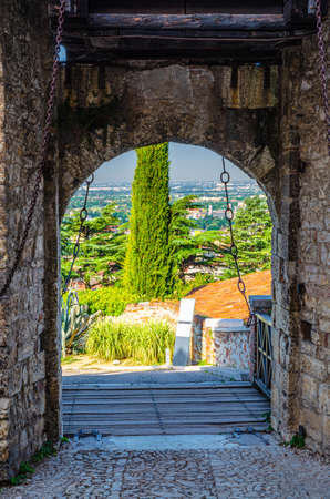 Brescia, Italy, September 11, 2019: Stone wall with merlons and drawbridge Gate of medieval Castle of Brescia or Castello di Brescia or Falcon of Italy, historical city center, Lombardy