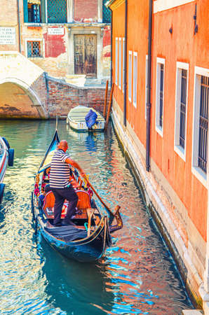 Venice, Italy, September 13, 2019: bold gondolier on gondola with tourists people sailing in narrow water canal between old colorful buildings in historical city center, Veneto Region 新闻类图片