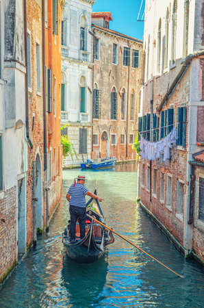 Venice, Italy, September 13, 2019: Gondola sailing narrow canal between old buildings with brick walls. Gondolier dressed traditional white and blue striped short-sleeved polo shirt and boater hat