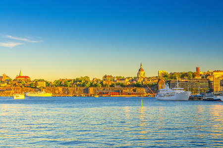 Cityscape of Stockholm historical city center with Sodermalm island coast near Lake Malaren water and boats ships near Gamla Stan embankment with blue clear sky background, Sweden