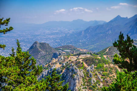 Kyrenia Girne mountain range from medieval Saint Hilarion Castle with green trees and rocks, blue sky white clouds in sunny day, Northern Cyprus