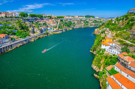 Aerial panoramic view of Porto Oporto city with Infante Dom Henrique Bridge ponte across Douro River with steep slopes between Ribeira district and Vila Nova de Gaia city, Norte or Northern Portugal
