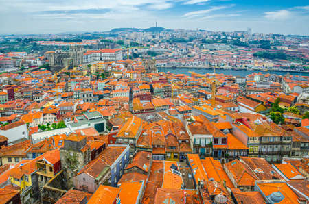 Aerial panoramic view of Porto Oporto city historical centre with red tiled roof typical buildings, Porto Cathedral, Douro River and Vila Nova de Gaia city background, Norte or Northern Portugal