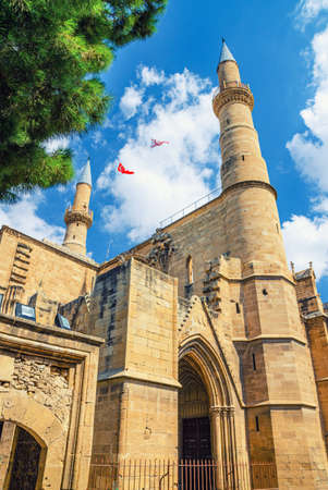 Selimiye Mosque or Cathedral of Saint Sophia or Ayasofya Mosque building with minarets in North Nicosia historical city center, blue sky white clouds background, Cyprus