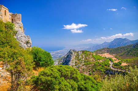 Aerial view of Kyrenia Girne mountain range and valley in front of Mediterranean sea, green trees on rock and ruins of Saint Hilarion Castle foreground, blue sky in sunny day, Northern Cyprus