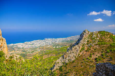 Aerial view of Kyrenia Girne mountain range and valley in front of Mediterranean sea, green trees on rock foreground, blue sky in sunny day, Northern Cyprus