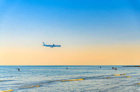 Airplane flying low above sea and people tourists swimming in water, clear blue orange sky at sunset, plane preparing to land at Larnaca airport above Mediterranean sea 免版税图像