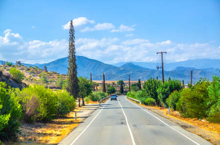 Landscape of Cyprus with cars vehicles riding asphalt road in valley with yellow dry fields, cypress trees and roadside poles, Troodos mountain range and hills, clear blue sky in sunny day background